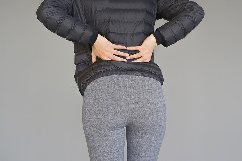 Woman, pain at lower back. Close-up woman with pain in kidneys isolated on a gray background. Young woman with back ache clasping her hand to her lower back stock photo