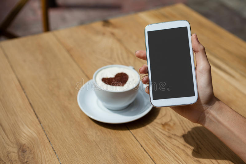 Close up of woman photographing coffee cup on table. At sidewalk cafe stock photos