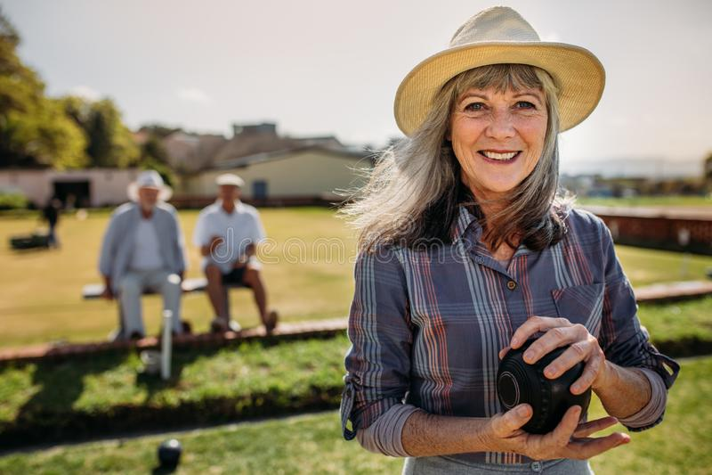 Close up of a woman playing boules in a lawn royalty free stock images