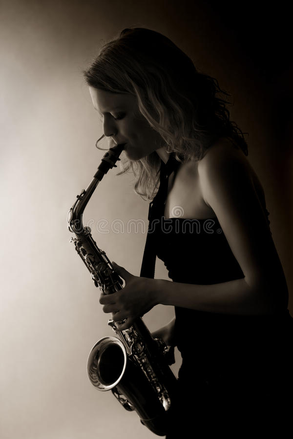 Close-up of woman playing saxophone, sepia toned. royalty free stock image