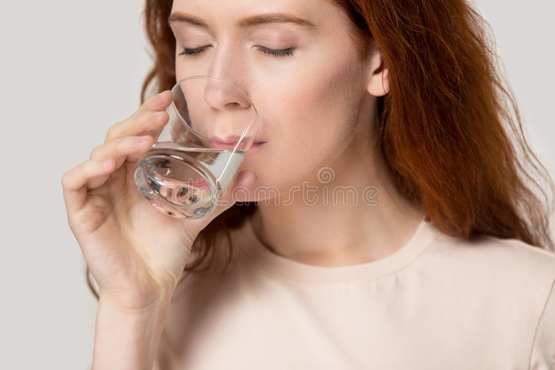 Close up young thirsty red-headed woman drinking clean water royalty free stock photo