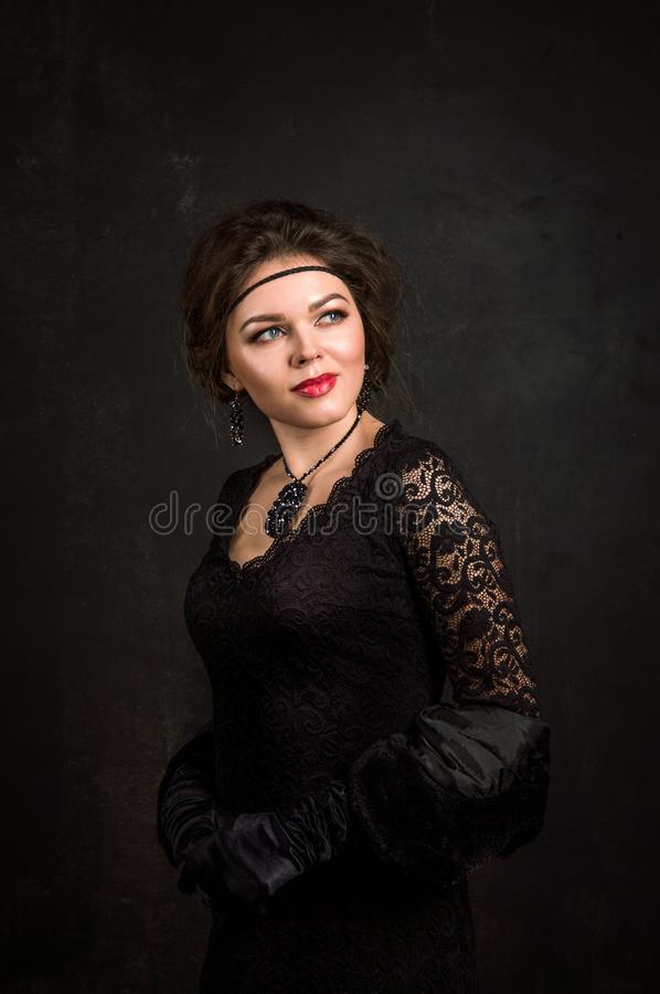 Close up. Woman portrait in the style of Gatsby. Low key. Beautiful young woman in a black dress, gloves and a black fur cape. royalty free stock photo