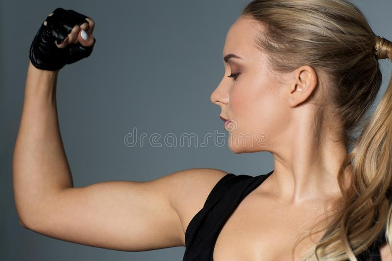 Close up of woman posing and showing biceps in gym stock images