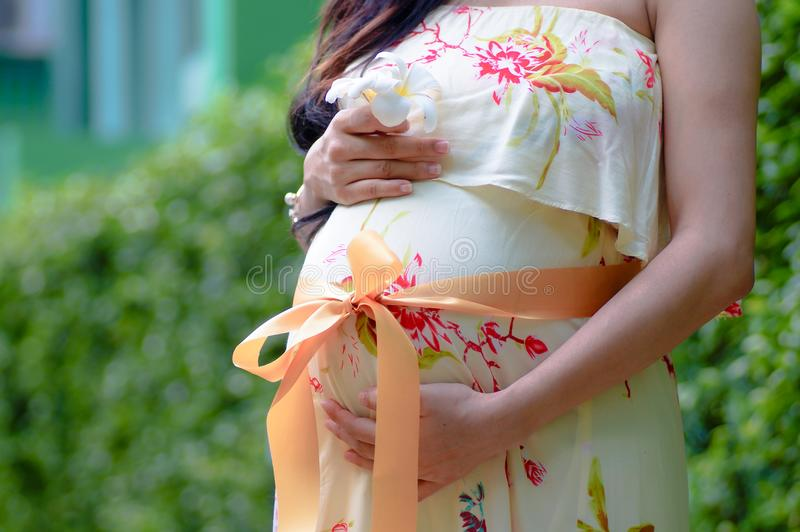 close up woman is pregnant standing in park royalty free stock photo