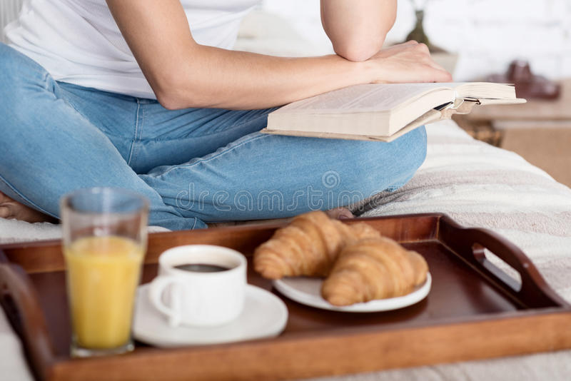 Close up of woman reading book on bed stock photo