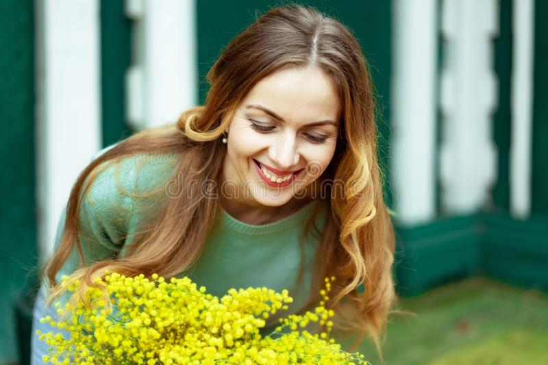 Close-up woman receives flowers and rejoices and smiles at gift. March 8, Mother`s Day stock photos