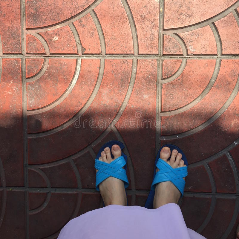 Close up of a Woman's Blue Slippers Buddhist Walking on Street or Ground for Relaxation and Meditation. Great For Any Use royalty free stock photography
