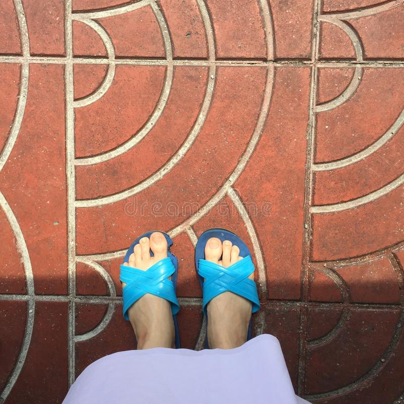 Close up of a Woman's Blue Slippers Buddhist Walking on Street or Ground for Relaxation and Meditation. Great For Any Use royalty free stock image