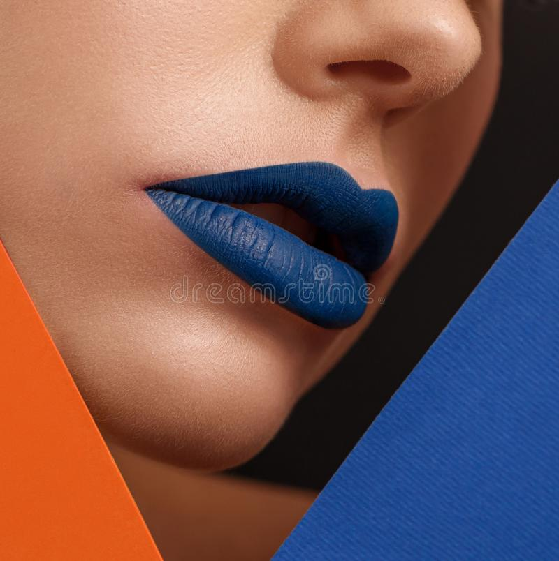 Close up of woman`s face with lips covered with dark blue lipstick. royalty free stock image