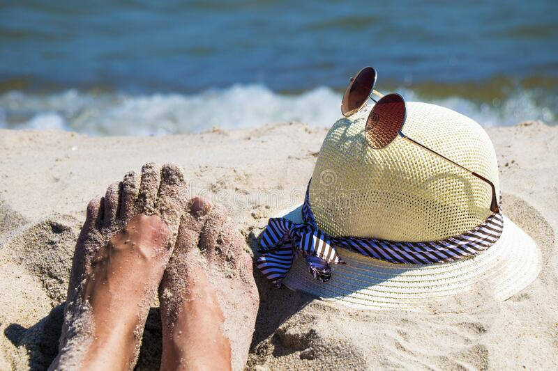 Close up of woman`s feet and hat with sunglasses on sandy beach with blue sea - relaxation, holidays stock photos