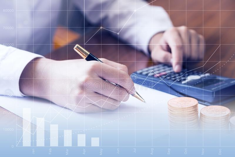 Close up of woman s hand with a calculator. She is holding a pen ready to take notes in her notebook. Clipboard. Toned image doubl royalty free stock photo