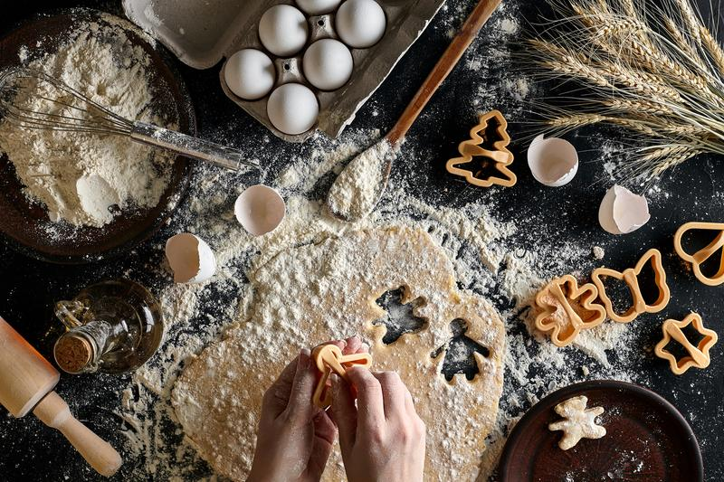 Close-up of a woman`s hand with a dough. The woman is cutting a cookie with a cookie cutter in the shape of a little royalty free stock image