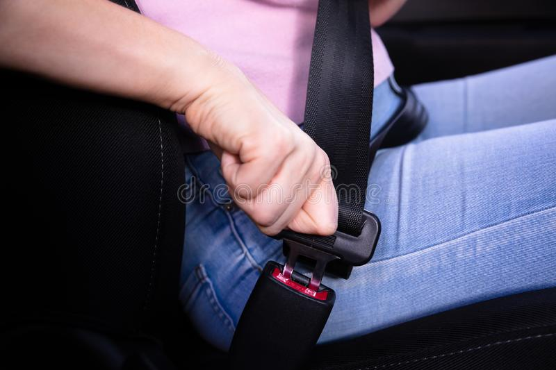 Woman Fastening Seat Belt In Car stock images