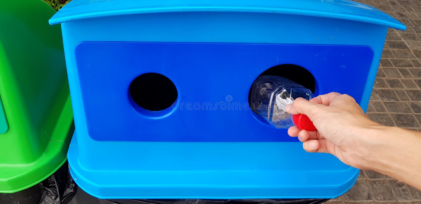 Close up woman`s hand holding and dumping plastic bottle of water into blue recycle bin, trashcan or trash. Cleaning area and Recycling used concept stock photo