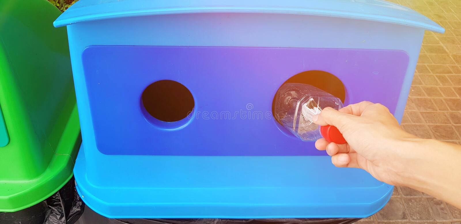Close up woman`s hand holding and dumping plastic bottle of water into blue recycle bin, trashcan or trash with orange sunlight fl. Are - Cleaning area and royalty free stock photo