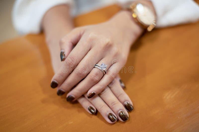 Close up of woman`s hand holding elegant engagement diamond ring royalty free stock photo