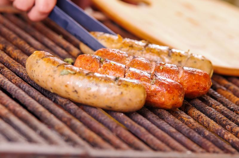 Close up of woman s hand holding a tongs turning the grilling sausages on barbecue grill. BBQ. Bavarian sausages.  stock photo