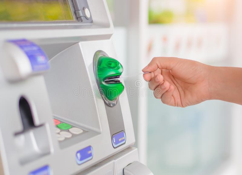 Close-up of woman`s hand inserting debit card into an ATM machin stock photo