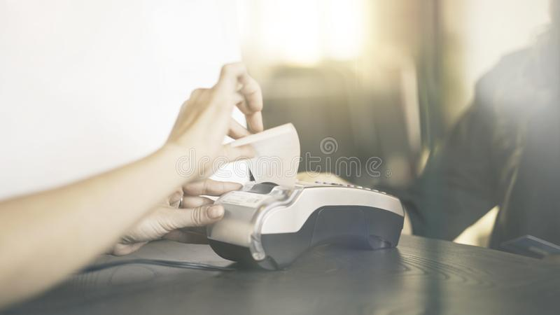 Close up of woman s hand paying with a credit card in a store. Check receipt stock image