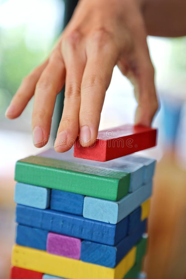 Close-up of woman`s hand pick the red stack on the wooden tower game in morning light , playing and learning background concept royalty free stock photo
