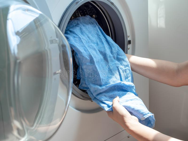 Woman`s hand putting dirty blue linen shirt in washing machine stock photography