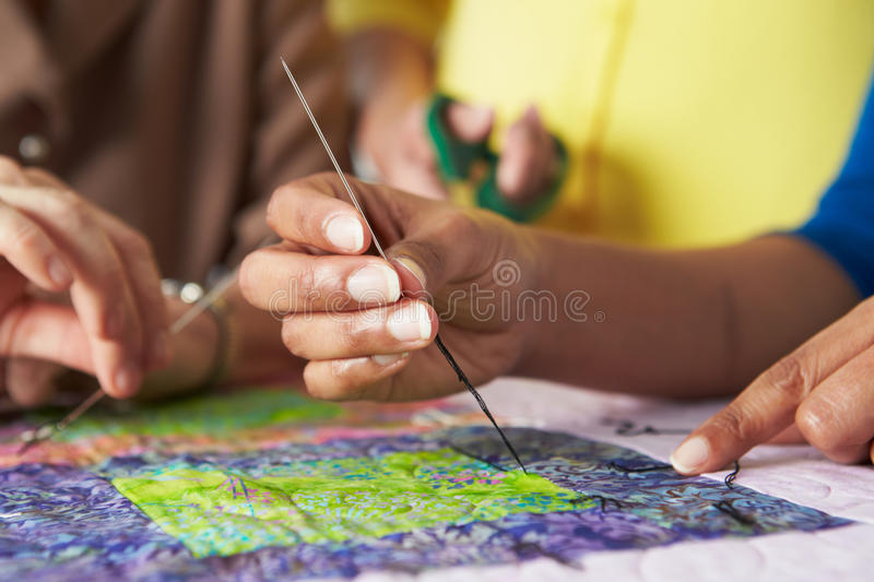 Close Up Of Woman's Hand Sewing Quilt stock photography