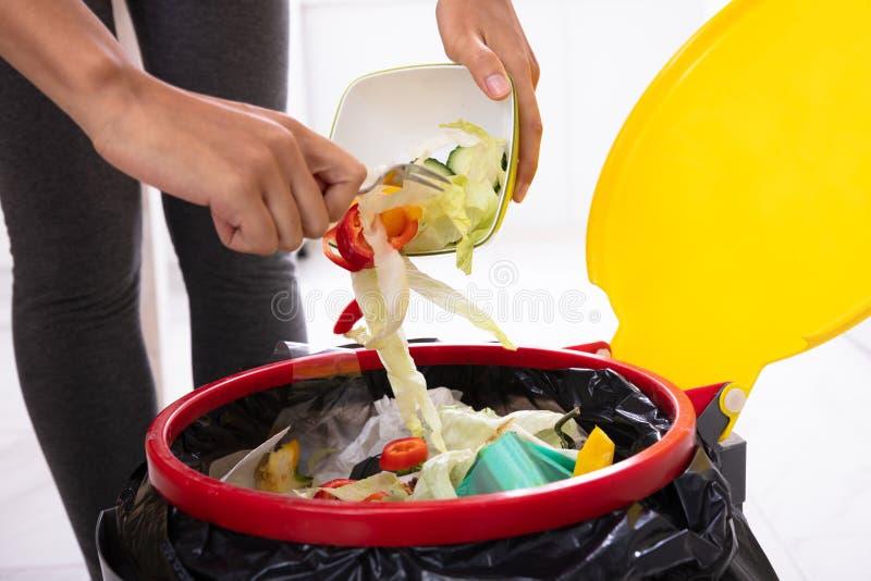 Woman Throwing Salad In Trash Bin. Close-up Of A Woman`s Hand Throwing Salad In The Open Trash Bin stock image