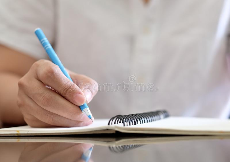 Close up of woman`s hand write on notebook. royalty free stock photo