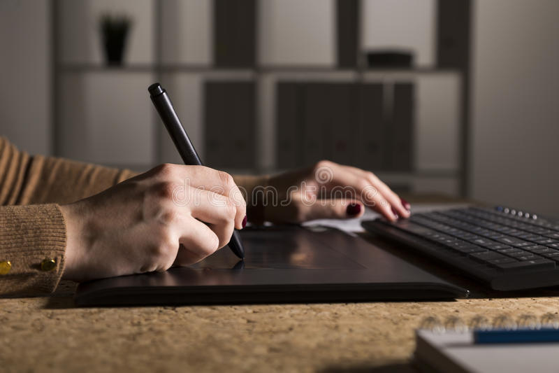 Close up of woman`s hands drawing on her pad and typing royalty free stock photography