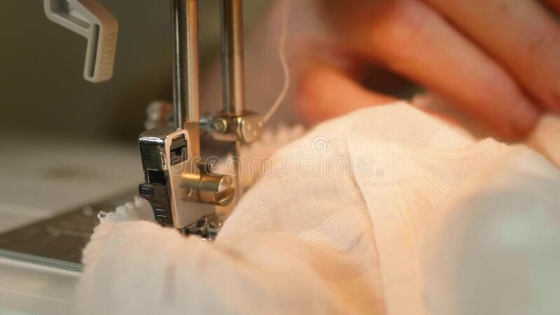 Close up of woman`s hands holding white material and sew on sewing machine. royalty free stock images