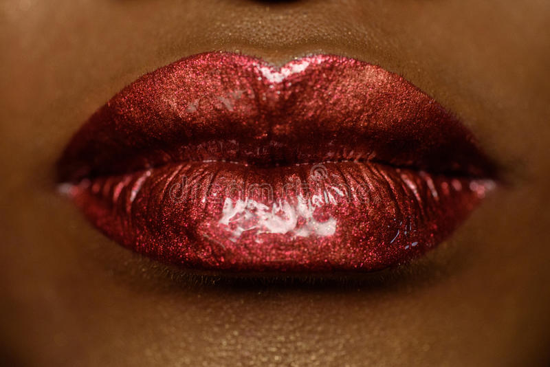 Close-up of woman's lips with bright fashion dark red glossy makeup. Macro lipgloss cherry make-up. kiss stock photography