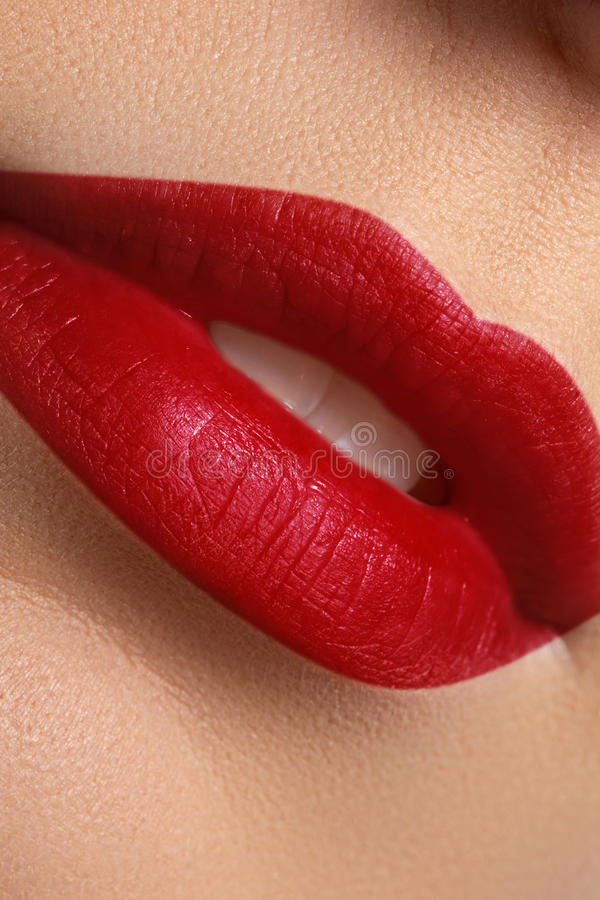 Close-up of woman`s lips with bright fashion red glossy makeup stock photography