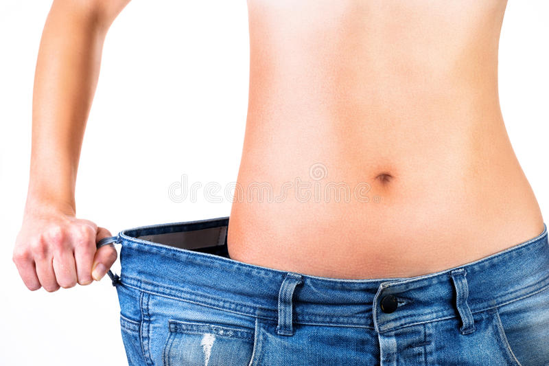 Close up of a woman's waist inside blue jeans. Weight loss concept. Close up of a woman's waist inside blue jeans isolated on white background stock photography