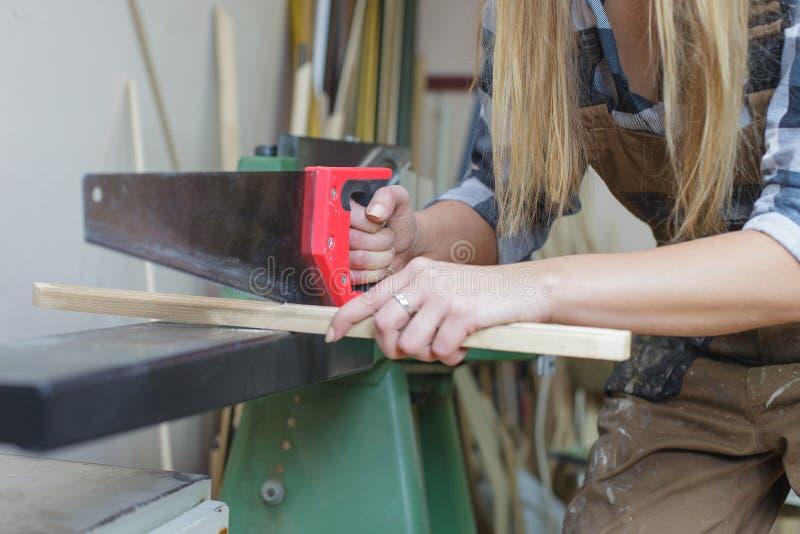 Close up of a woman sawing wooden slat. Close up of a woman cutting wooden slat stock photos