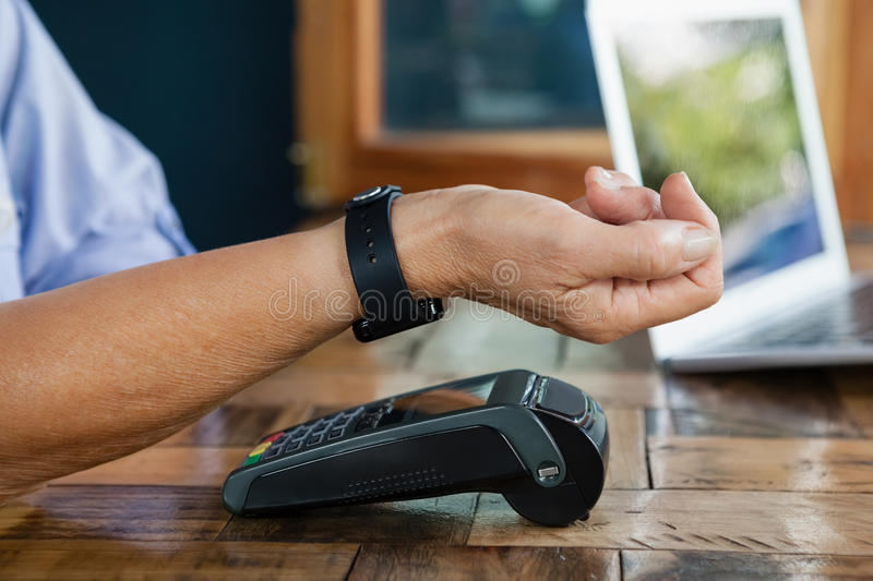 Close up of woman scanning smart watch on credit card reader. At cafe shop royalty free stock photos
