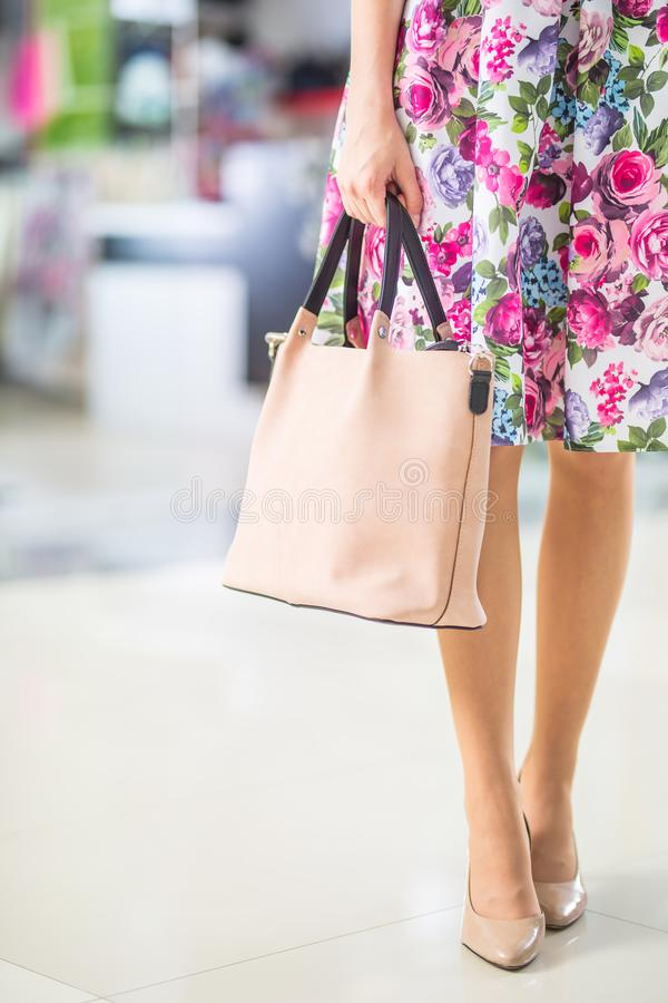 Close-up woman sexy legs summer outfit handbag and shoes. Stylish casual woman in shopping mall royalty free stock photography