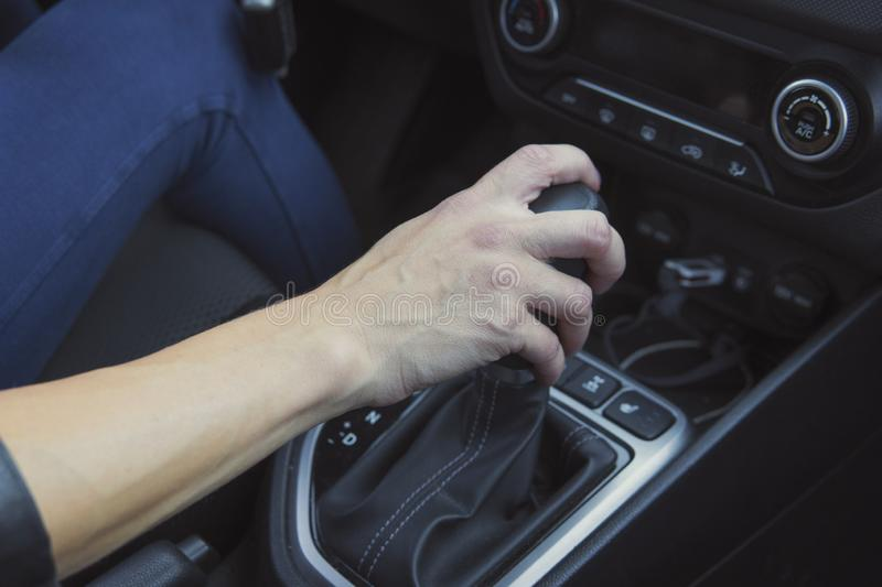 Close up of woman shifting gears on automatic gearbox and driving car. Female hand shifts the hydro sitting in a vehicle. Auto stock photography