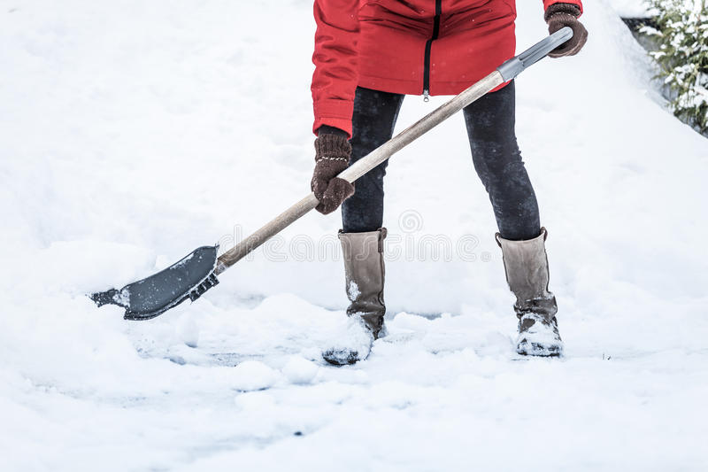 Close-up of Woman Shoveling her Parking lot royalty free stock images