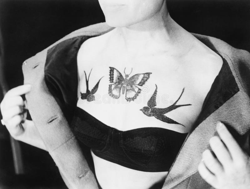 Close-up of a woman showing tattoos on her chest. (All persons depicted are no longer living and no estate exists. Supplier grants that there will be no model royalty free stock image