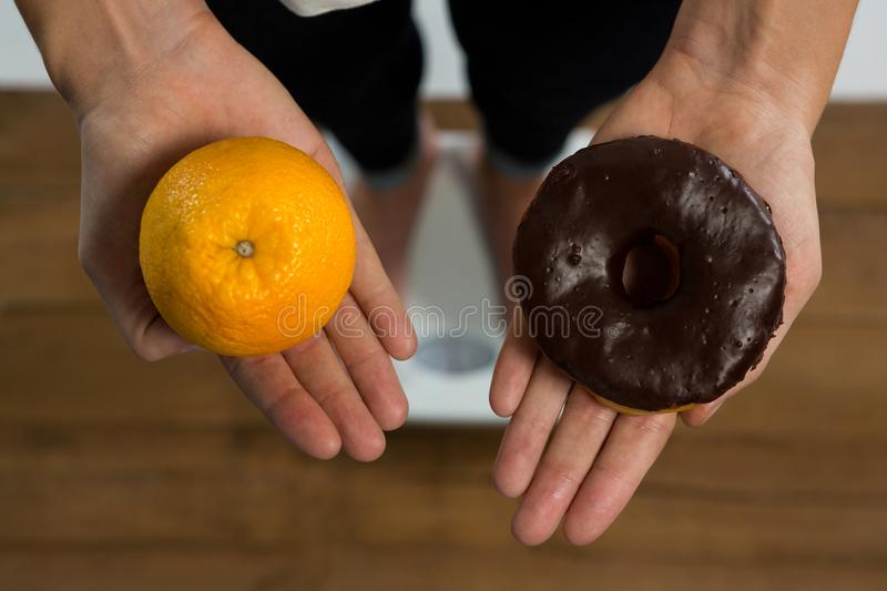 Woman standing on weight machine and holding doughnut and orange royalty free stock photo