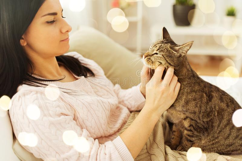 Close up of woman with tabby cat in bed at home royalty free stock image