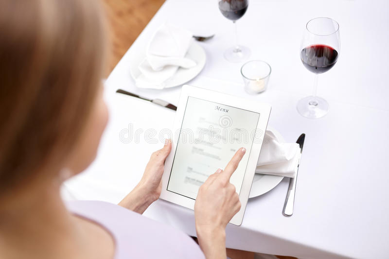 Close up of woman with tablet pc at restaurant. Technology, people, food and dinner concept - close up of women with tablet pc at restaurant stock images