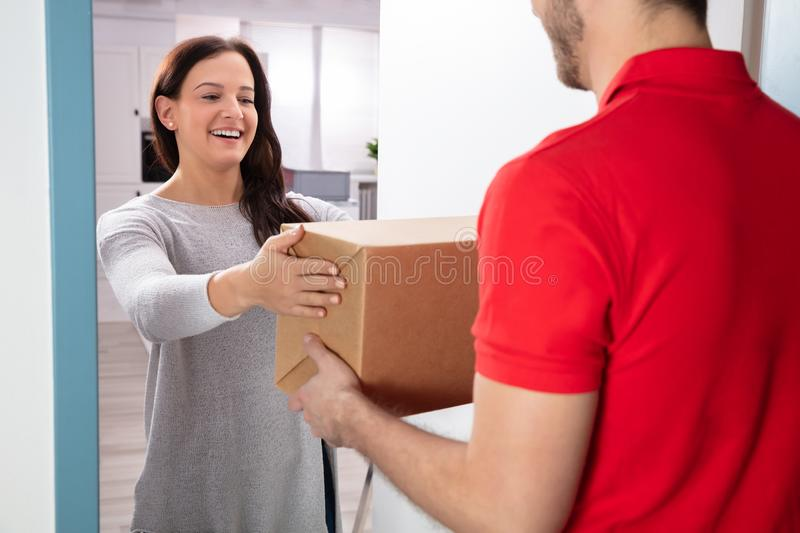 Woman Taking Box From Delivery Man. Close-up Of Woman Taking Cardboard Box From Delivery Man stock images