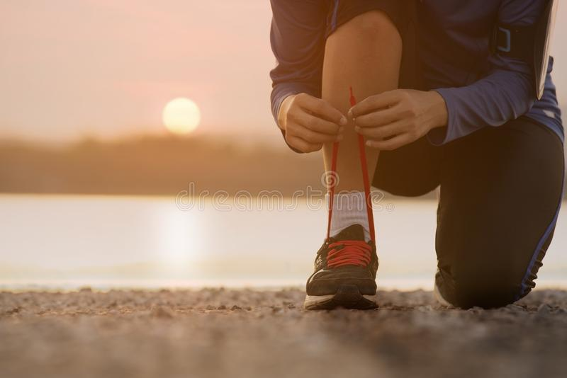 Close up woman tying shoe laces stock photo