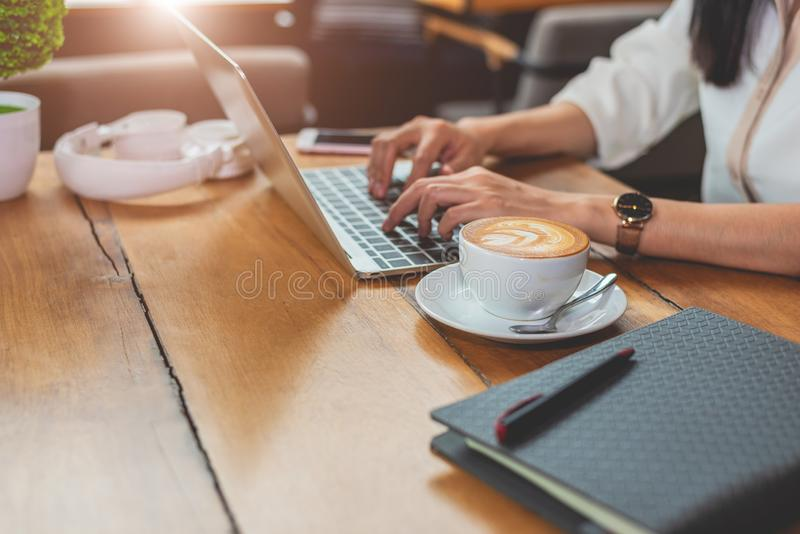 Close up of woman typing keyboard on laptop in coffee shop. People and technology concept. Freelance and Lifestyle theme. stock image