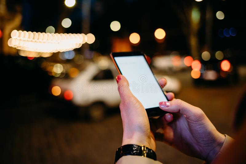 Close-up of woman using mobile phone. With white blank screen on background of night city lit by lanterns in bokeh and road with cars stock image
