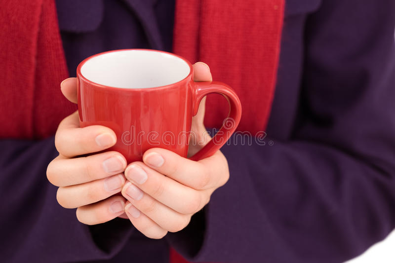 Close up of a woman in warm clothing holding mug. On white background royalty free stock image