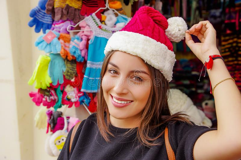 Close up of woman wearing a christmast hat in front of souvenir store in the Passage Craft in the downtown of the city. Of Banos, Ecuador stock photo