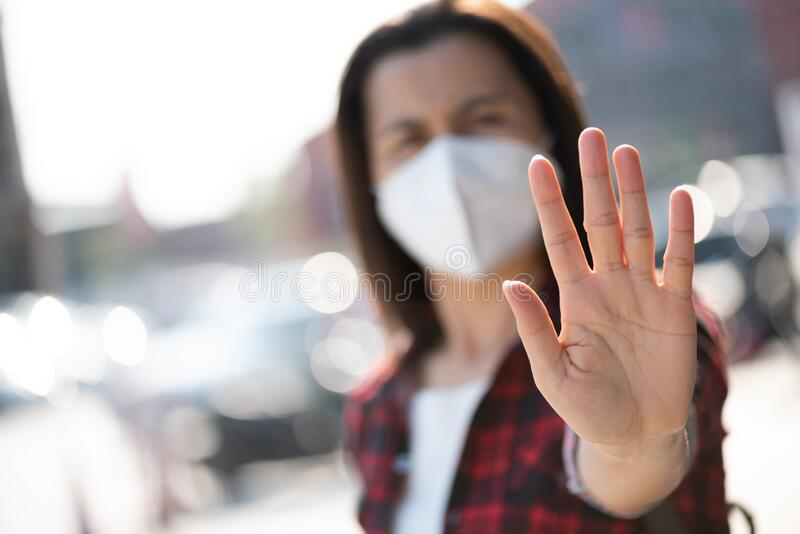 Close up of woman wearing protective face mask, get ready for Coronavirus and pm 2.5 fighting and show stop hands gesture for stop. Corona virus outdoor beside royalty free stock image