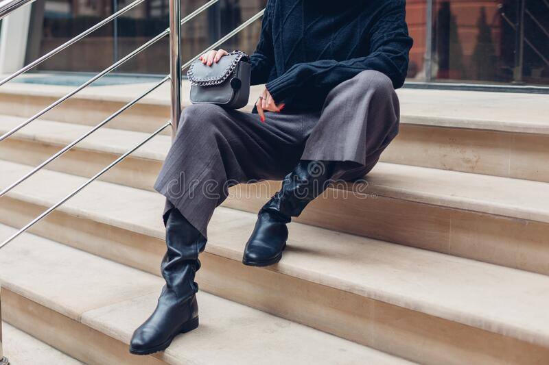 Close up of woman wearing stylish shoes boots holding purse outdoors. Spring fashion female accessories and clothes. Close up of woman wearing stylish shoes stock photo